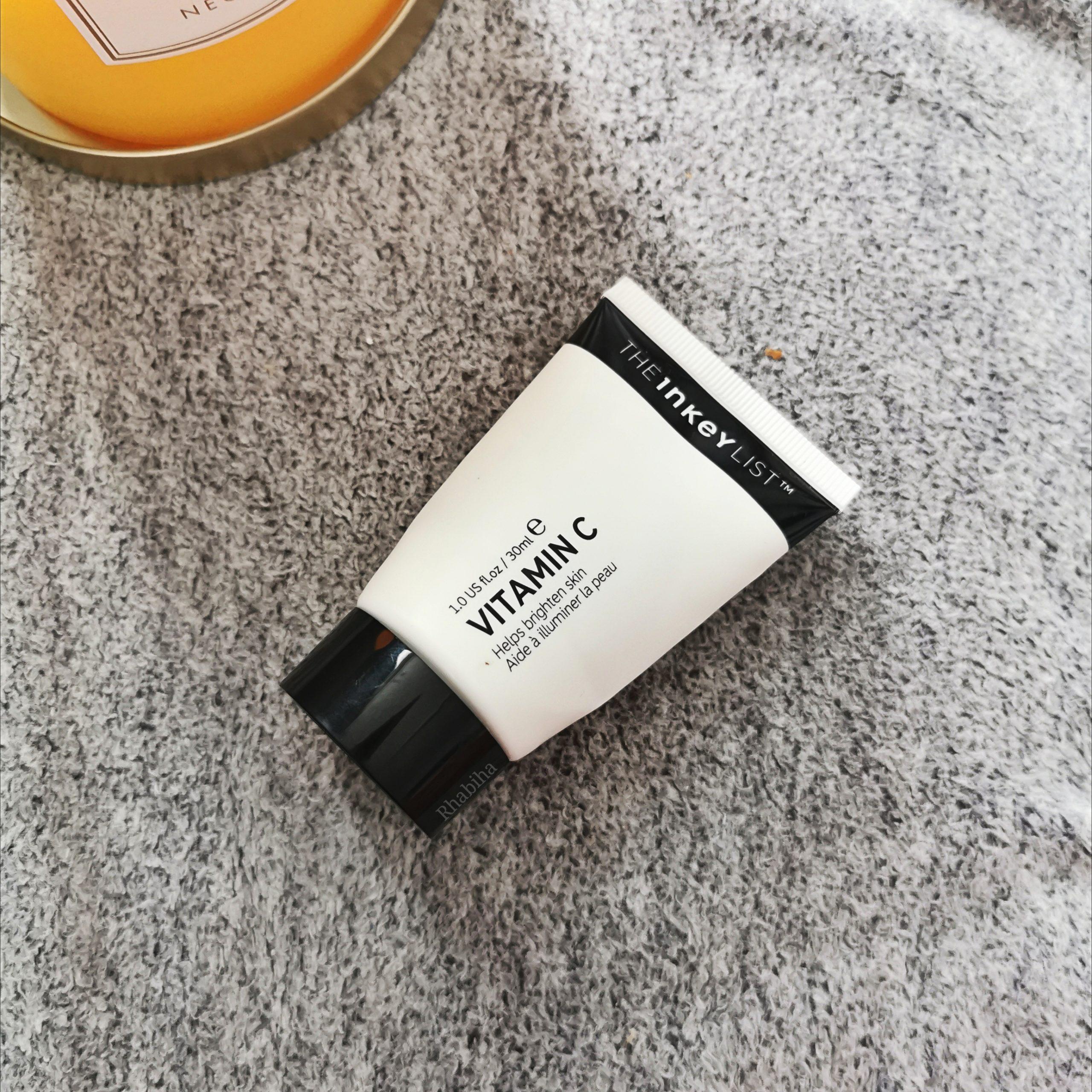 Tube blanc de sérum de vitamine C de la marque The Inkey List près d'une bougie jaune