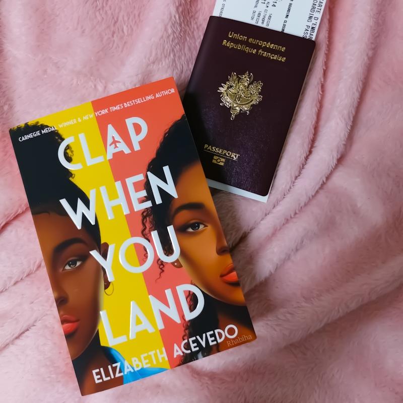 """Couverture du livre """"Clap When You Land"""" d'Elizabeth Acevedo avec un passeport à côté du livre"""