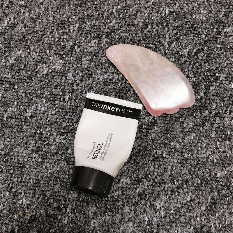 Tube de sérum rétinol de la marque Inkey et pierre de quartz rose pour masser le visage